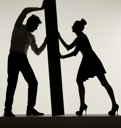 A man and woman pushing on opposite sides of a wall.