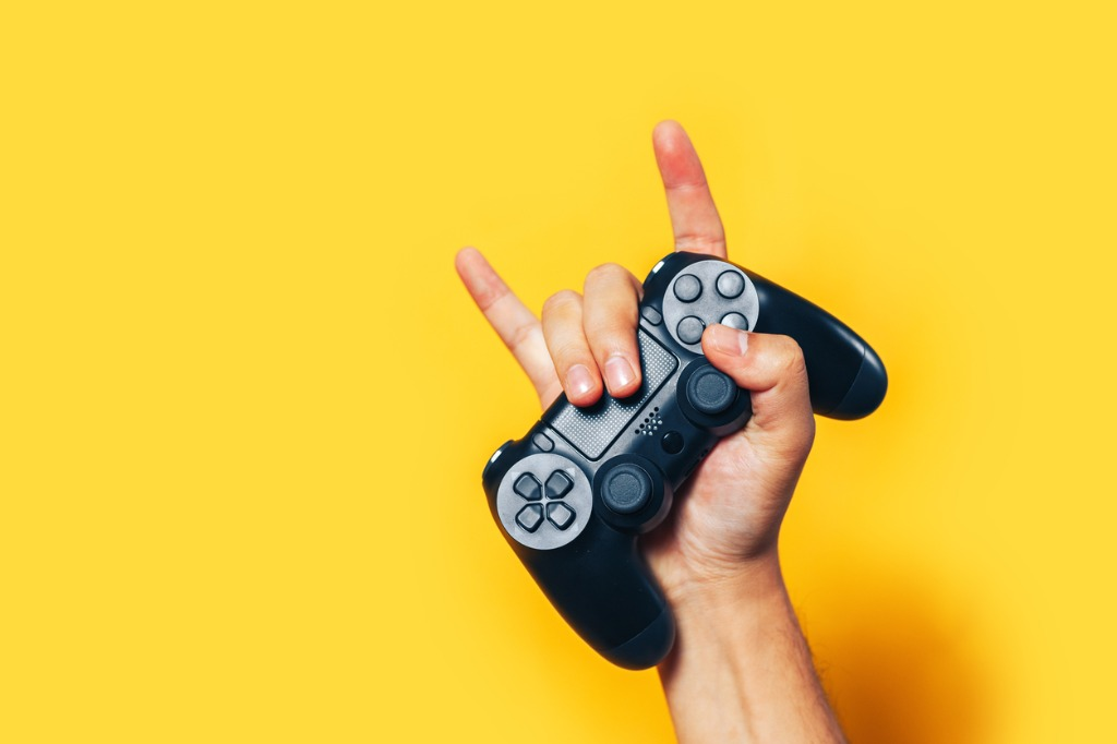 hand holding a video game controller and making the sign of the horns