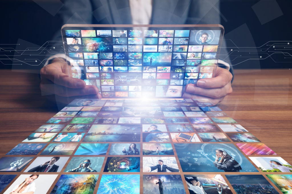 man holding a tablet with dozens of videos on it